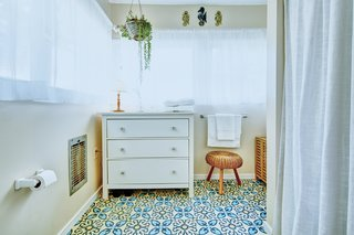 Bright, graphic floor tiles have also been used in the bathroom.
