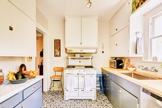 A charming kitchen features graphic floor tiles and is equipped with a vintage Wedgwood stove.