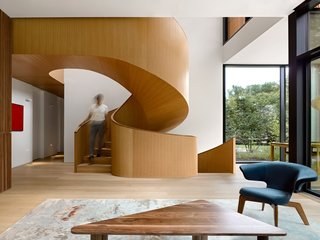 A wood-clad spiral staircase connects the living room to the second-floor master suite.