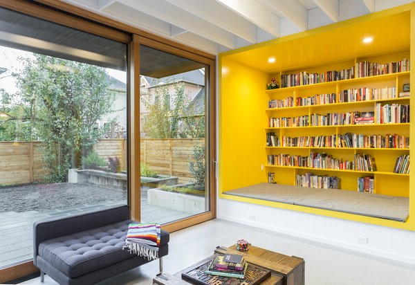 A floor-to-ceiling sliding door offers direct access to the patio and yard. A yellow custom-built reading nook packs a playful punch of bold color, and certainly brightens up the gray days that the Pacific Northwest is known for.