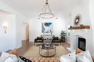 The living room also offers new lighting from Restoration Hardware, a decorative fireplace, and newly installed wide-plank oak floors.