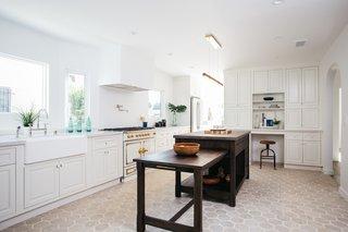 The chef's kitchen boasts a La Cornue range, custom cabinetry, a farm sink, designer hardware, and a concrete top island.
