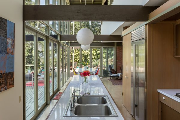Kitchen, Laminate Counter, Drop In Sink, Refrigerator, Wood Cabinet, and Pendant Lighting The open layout flows from the kitchen into the dining and living areas.  Photo 4 of 17 in Mad Men Producer Puts His Pasadena Midcentury Up For Auction Starting at $1.7M