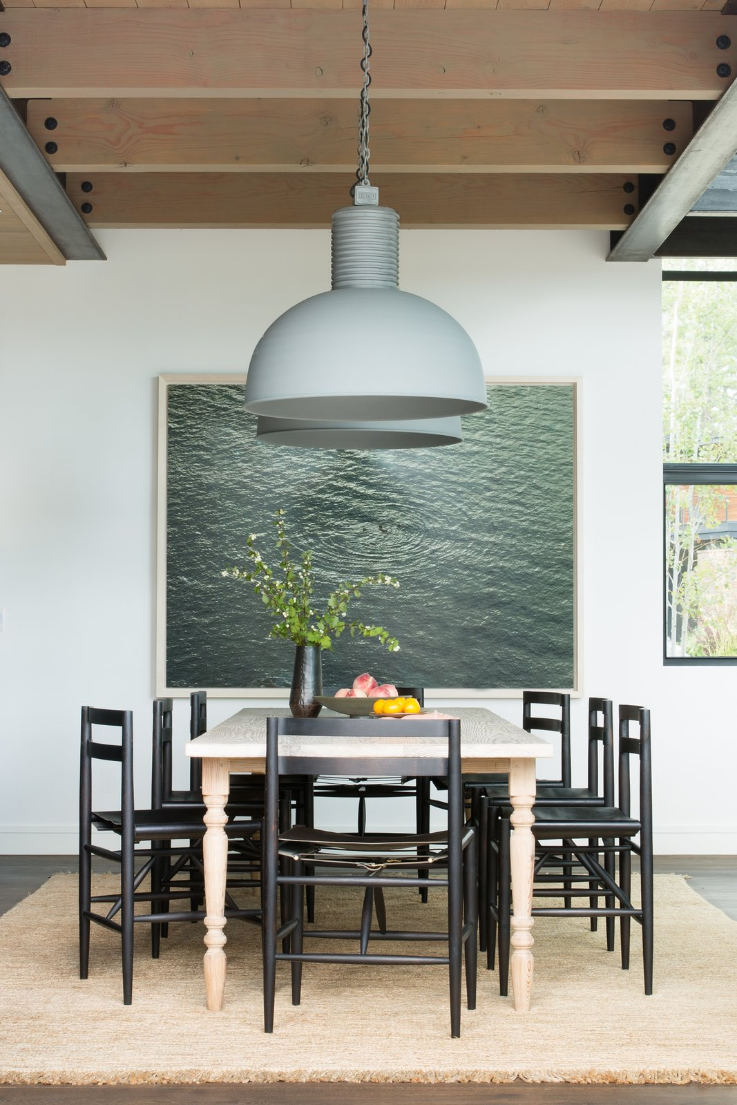 Dining Room, Chair, Medium Hardwood Floor, Rug Floor, Pendant Lighting, and Table The dining room table is a new, custom-made piece from Nickey Kehoe. It is paired with ebonized black wood chairs with leather sling style seats by Sawkille Co. The chunky braided jute rug with fringe is from Armadillo & Co., the large pendant lights are from Frezoli Lozz, and the artwork is a photograph by Richard Misrach.   Photo 5 of 20 in A Sleek Lake Tahoe Retreat Shows Off an Impressive Art Collection
