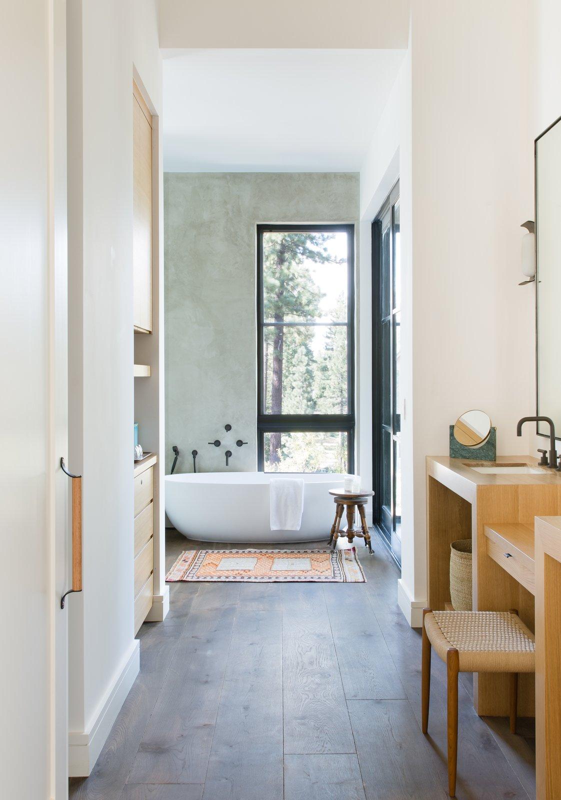 Bath Room, Freestanding Tub, Medium Hardwood Floor, and Wood Counter A peek into the master bath.  Photo 19 of 20 in A Sleek Lake Tahoe Retreat Shows Off an Impressive Art Collection