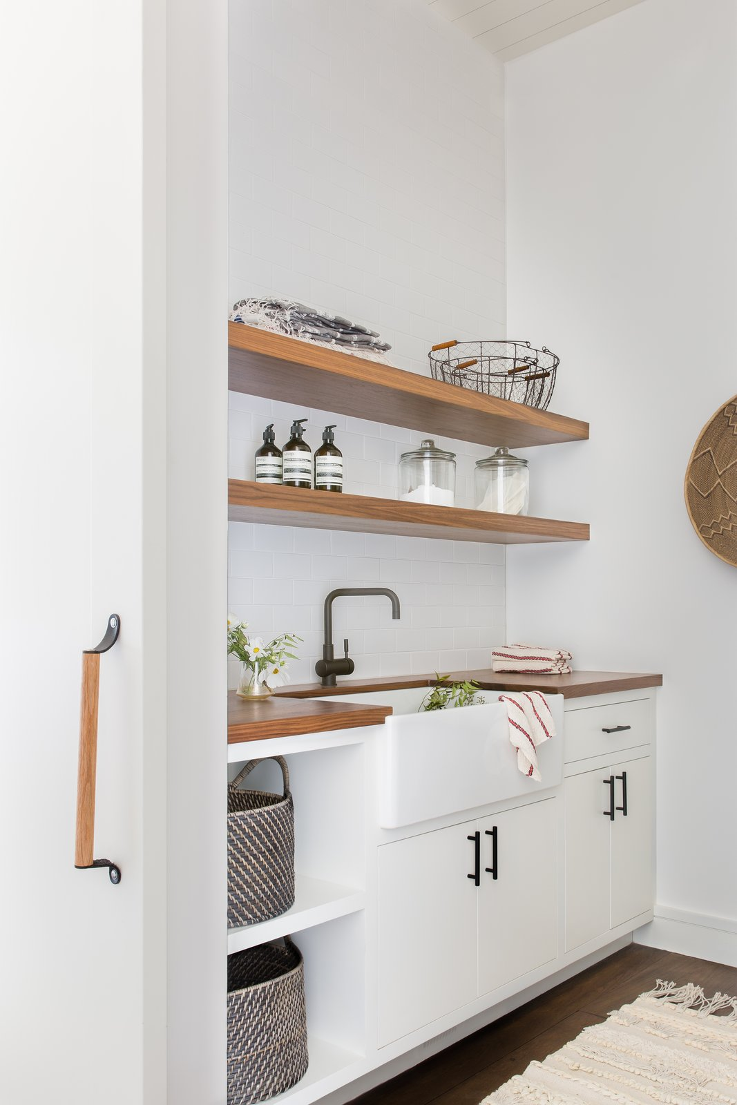 Laundry Room, Wood Counter, and White Cabinet The laundry room is simple and efficient.  Photo 9 of 20 in A Sleek Lake Tahoe Retreat Shows Off an Impressive Art Collection
