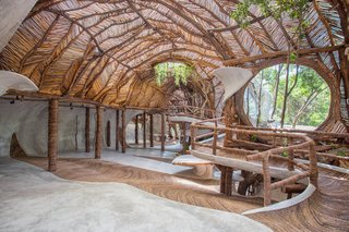 Sterkel's design for IK Lab continues the environmentally friendly spirit of the resort. Tree branches support the wavy canopy, while smaller sticks arranged in a diagonal pattern allow light to filter through. Large, round windows perforate the interior, and the floor is covered with a local, vine-like plant called Bejuco wood.