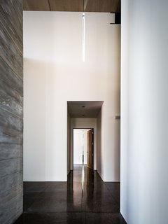 The eye is drawn down the corridor towards the slice of light.