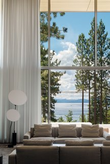 The minimalist material palette and two-story glass wall respond to the client's desire to focus on the view of the lake, from water to treetops.