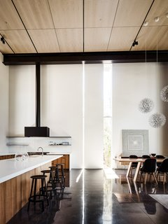 Within the setting of the open floor plan, slits of light reflecting on the ebonized, concrete floor help to demarcate distinct spaces. Here, the kitchen is set off from the dining and living areas.