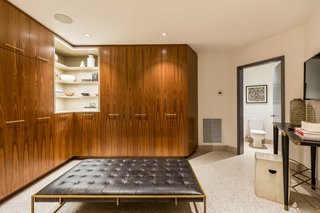 One of the walk-in closets features walnut cabinetry.