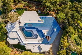 An aerial view of the property clearly shows the home's hexagon-shaped floor plan and central swimming pool courtyard.