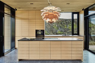 The open kitchen blends in with sleek, wood cabinetry and black countertops.