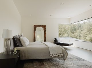 A sweeping expanse of glass spans the corner in the master suite, integrating a sense of the outdoors into the bedroom.