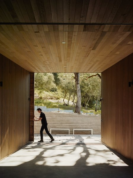 A sliding wooden door marks the entrance to the interior courtyard of the home. The residence consists of three connected volumes of different heights wrapping around the center of the podium, and the spaces inside them carefully scaled: small enough for introspection, and large enough to take in the landscape.