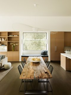 A dining area divides the open kitchen from the living room.