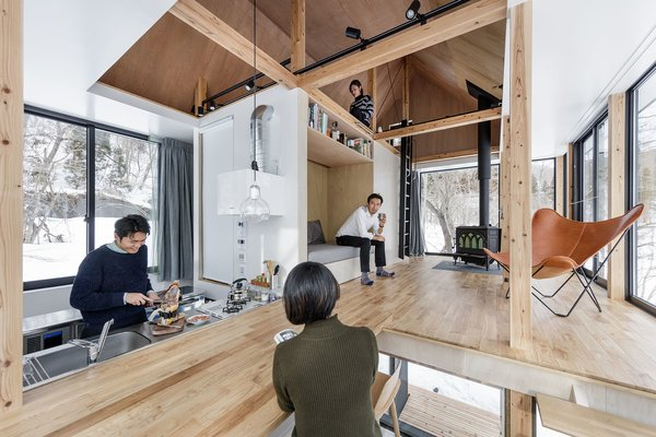 Inside, the open-plan layout features a kitchen which morphs into the living area with a raised built-in bench/reading nook, along with an upper level that overlooks the space.