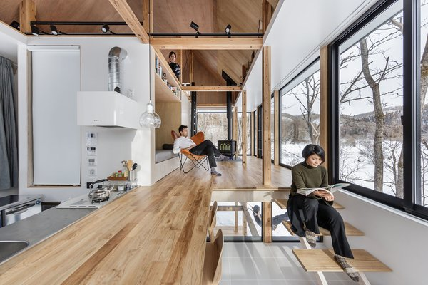 The kitchen is layered with the living room—the counter space becomes the flooring in the living area, and steps are used as additional seating.