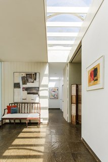 Sunlight streams in through skylights and glass walls, allowing the homeowners to feel connected to the setting.
