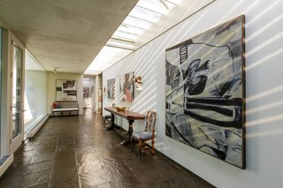 Theskylights brighten the long corridor and highlight the homeowner's art collection.