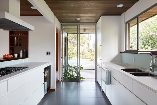 Kitchen Ample natural light helps to keep the interiors bright. The kitchen countertops have been refinished in Caesarstone Blizzard.    Photo 6 of 14 in This Eichler Home in California Mixes Scandinavian Vibes With Midcentury Charm