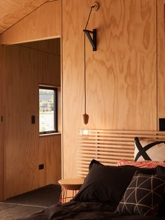 The bedrooms maintain the same look as the rest of the home with the use of plywood and black accents.