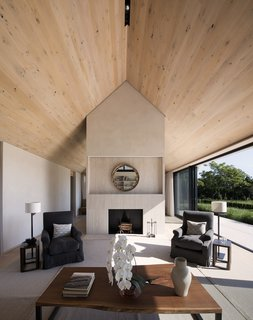 The interiors are bright and airy thanks to high wood-paneled ceilings and expansive glazing that open to the outdoors.