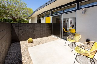 A mason block wall encloses a small front patio with access from the kitchen via a sliding glass door, creating a  strong indoor-outdoor connection.