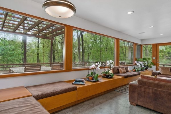 The living room is lined with glazed windows, providing a strong connection with the surrounding outdoors.