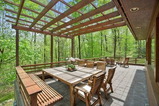The home is positioned on a gently sloping site and an exterior deck provides views of the surrounding forest. The pergola was built with a removeable awning.