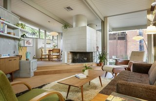 The interiors have a natural material palette of redwood and Douglas Fir siding, and also features cork flooring. An original wood-burning fireplace has been kept intact to anchor the living room.
