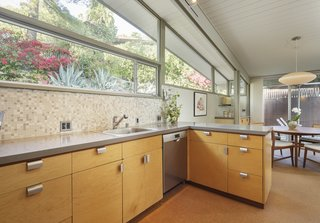 The kitchen opens to the dining area, where clerestory windows provide additional natural light.
