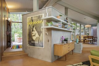 A central concrete wall serves as a divider between the kitchen and living room.