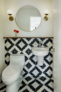 The powder room received a simple, yet stunning transformation with white paint, modern sconces from Cedar & Moss, and the addition of graphic black and white cement tile from Ann Sacks that wraps the wall.