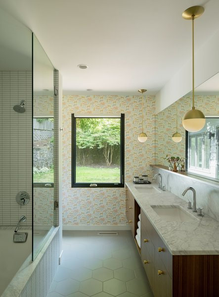 Now, the space looks both sophisticated and playful thanks to the addition of whimsical animal-printedwallpaper, marble countertops, tiles from Ann Sacks, and brass pendant lights designed by Cedar & Moss for Rejuvenation.