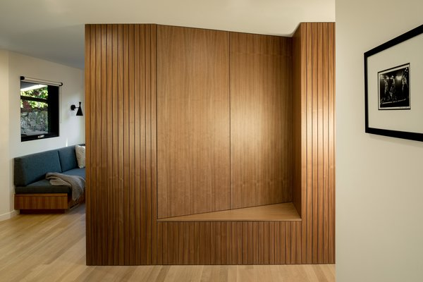 A walnut slat wall and built-in bench sit adjacent to the family room.