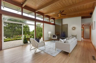 The open-plan living room maintains a strong midcentury vibe and features floor-to-ceiling glazing, tongue-and-groove beamed ceilings, an original brick fireplace, and refinished hardwood floors.