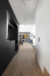"""Aglance down the hallway from the junction of the two prefab """"boxes."""""""
