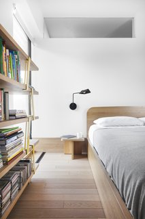 The bedroom is predominately oak with a custom-designed bed and nightstand. The lighting in this room is also by Sangaré.