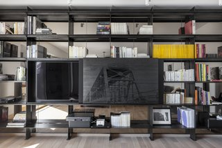 A commissioned art piece by local artist James Kennedy is mounted on a sliding door which hides the television set.