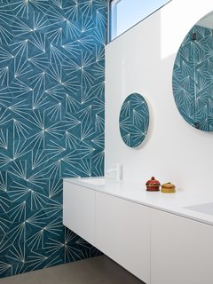 Bright, colorful wallpaper adds a fun touch of midcentury vibes to the bathroom.