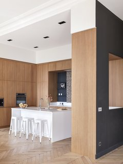 Designed by Hermand, the made-to-measure Oberflex kitchen anchors the semi-open layout. The kitchen island has been varnished in Farrow & Ball's strong white and features a Silestone Blanco countertop and stools from Tolix. The terrazzo backslash is from Carrément Victoire.