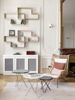 Traditional features such as the high ceilings, decorative moldings, and parquet flooring take on a softer, modern tone when set against a contemporary selection of furniture. The walls have been painted in the strong white shade from Farrow & Ball. The shelving is by Dédal by Matégot and the armchair is from Redoute.