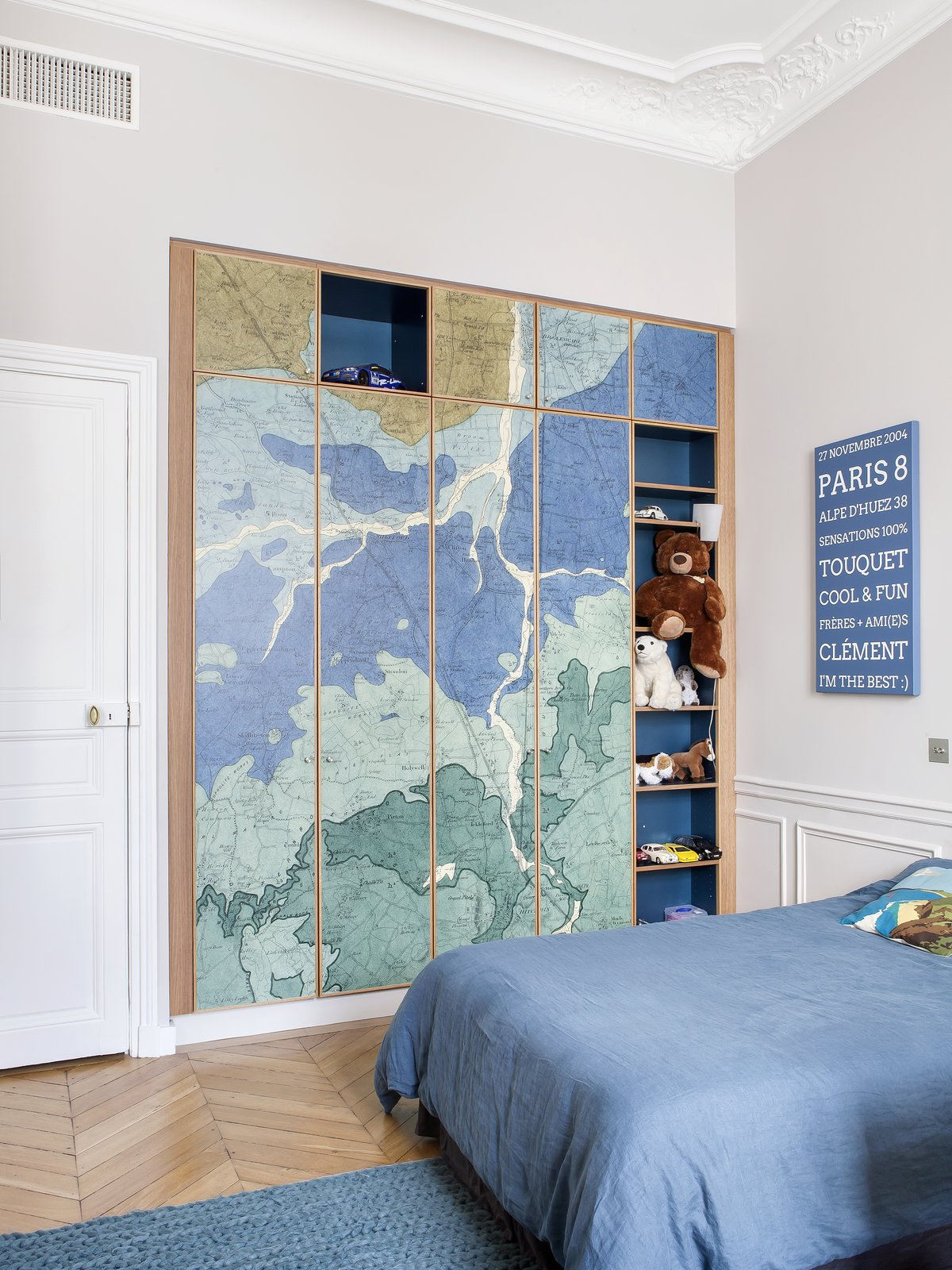 Kids Room, Bedroom Room Type, Storage, Medium Hardwood Floor, Rug Floor, and Bed Oh My Wall from Paris Wallpaper was fitted on wardrobe doors in one of the children's rooms.  Photo 12 of 13 in A Parisian Abode Is Reborn With a Fresh, Unexpected Color Palette