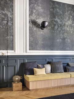 The design choices in the entryway showcase the home's grand scale and generous proportions. The wallpaper is Midsummer Night from Wall & Deco, the wall sconce is the Gubi Cobra noir, the custom bench is from Oberflex, and the custom cushions are from Bruder Textiles by les Petites Mains à la carte.