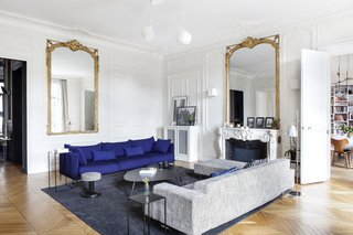 The main living room has become the central and multi-functional zone for the entire family. A Moroso Gentry sofa in royal blue, as well as a Poltrona Frau sofa and footrest have been reupholstered by Petites Mains à la carte. The lighting is FLOS AIM blanche, the coffee table is from AMPM, and the rug is from Annie Paté.