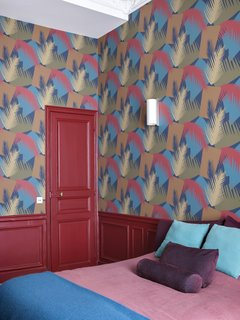 Bold choices for the guest room include Cole & Son's Deco Palm Wallpaper in red and blue.