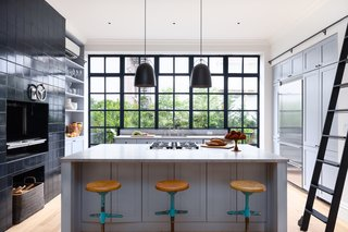 The kitchen includes top-of-the-line stainless steel appliances, custom floor-to-ceiling cabinetry, countertops in French Blue de Savoie marble, and a Pullman rolling ladder.