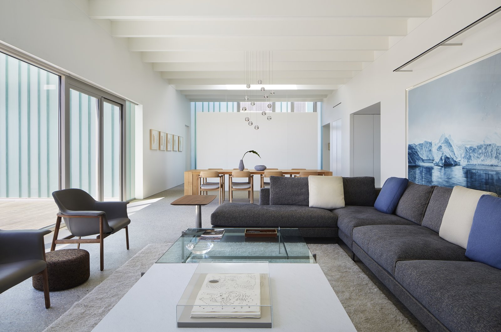 Living Room, Rug Floor, Sectional, Chair, Coffee Tables, End Tables, and Pendant Lighting A look at the living room looking toward the dining area.     Photo 6 of 12 in Four Courtyards Form This Modern Waterfront Home