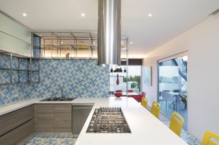 The bright colors and patterns are continued into the sleek design of the kitchen.